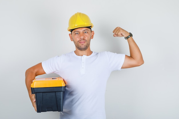 Budowniczy mężczyzna trzyma przybornik i pokazuje mięśnie w koszulce, kasku i wygląda pewnie, widok z przodu.
