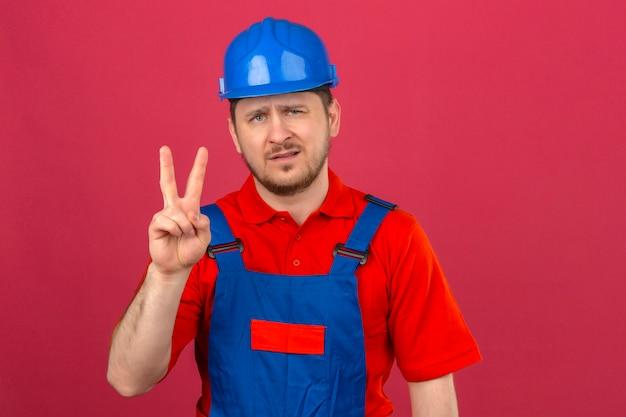 Budowniczy mężczyzna ubrany w mundur budowlany i hełm ochronny, pokazujący i wskazujący palcami numer dwa ze sceptycznym wyrazem twarzy na odizolowanej różowej ścianie