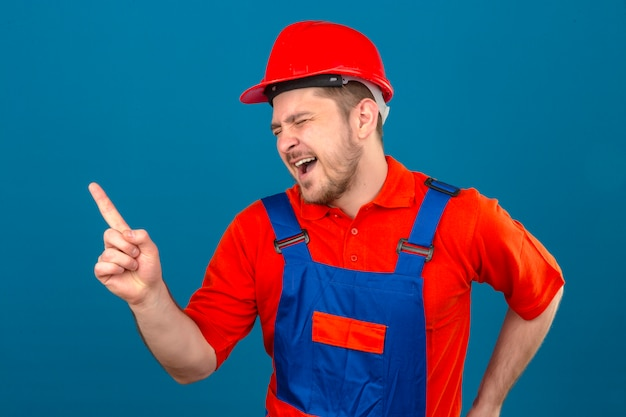 Budowniczy mężczyzna ubrany w mundur budowlany i hełm ochronny, śmiejący się z kogoś wskazującego palcem w bok, stojącego nad odizolowaną niebieską ścianą