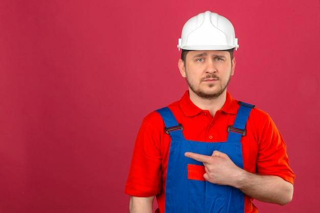 Budowniczy mężczyzna ubrany w mundur budowlany i hełm ochronny, wskazując palcem, aby skopiować przestrzeń ze smutnym wyrazem twarzy stojącej nad izolowaną różową ścianą