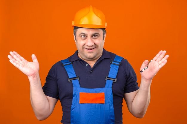 Budowniczy mężczyzna ubrany w mundur budowlany i kask ochronny wzruszający ramionami, rozkładający ręce, nie rozumiejąc, co się stało, nieświadomy i zdezorientowany wyraz twarzy na odizolowanych pomarańczowych plecach