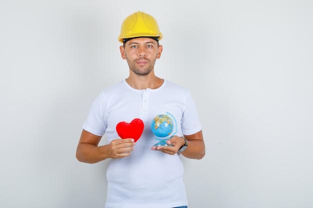 Budowniczy mężczyzna w białej koszulce, hełm trzymający czerwone serce i kula ziemska, widok z przodu.