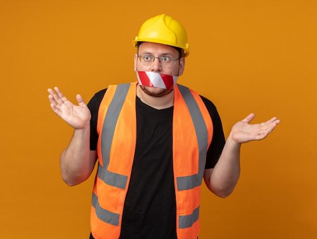 Budowniczy mężczyzna w kamizelce budowlanej i kasku ochronnym z taśmą na ustach, patrząc zdezorientowany rozkładając ręce na boki