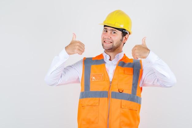 Budowniczy mężczyzna w koszuli, mundurze, pokazując kciuki do góry i wyglądający na szczęśliwego, widok z przodu.