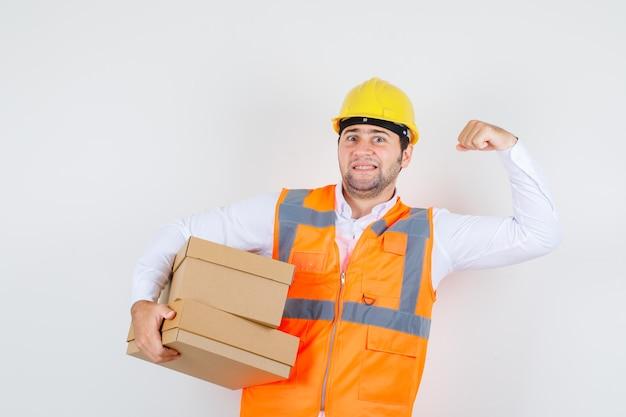 Budowniczy mężczyzna w koszuli, mundurze, trzymający kartonowe pudła, pokazujący mięśnie i wyglądający na pewnego siebie, widok z przodu.