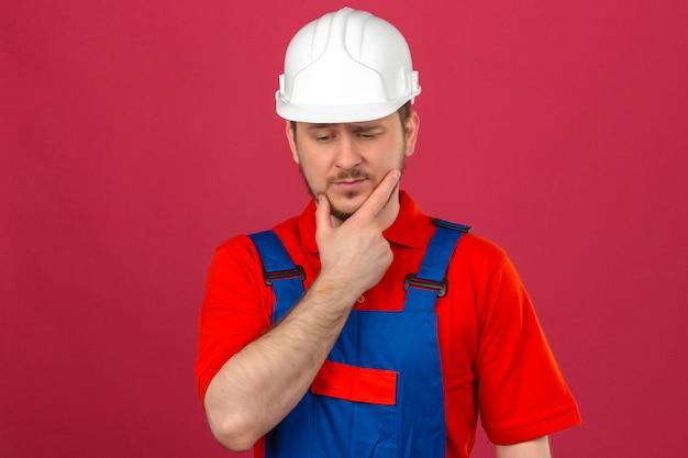 Budowniczy mężczyzna w mundurze budowlanym i hełmie ochronnym dotykającym jego policzka i zamyślonym spojrzeniem, próbując dokonać wyboru stojąc nad izolowaną różową ścianą