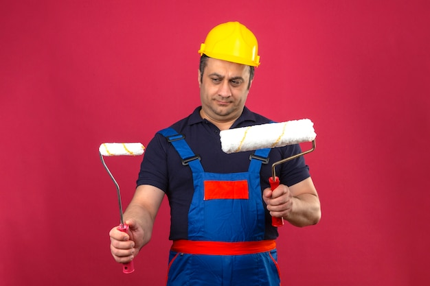 Budowniczy mężczyzna w mundurze budowlanym i hełmie ochronnym, stojący z wałkami do malowania, patrząc na nich z powątpiewaniem na izolowaną różową ścianę