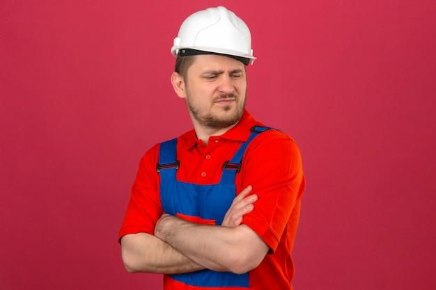 Budowniczy mężczyzna w mundurze budowlanym i hełmie ochronnym, stojący ze skrzyżowanymi rękami, patrząc na bok, z marszczoną twarzą pokazującą niechęć do odizolowanej różowej ściany