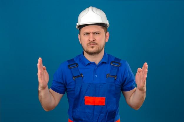Budowniczy mężczyzna w mundurze konstrukcyjnym i hełmie ochronnym przedstawiający duży znak z marszczoną twarzą symbol miary stojącej nad izolowaną niebieską ścianą