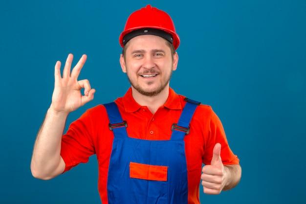 Budowniczy mężczyzna w mundurze konstrukcyjnym i hełmie ochronnym, uśmiechając się przyjaźnie, robiąc znak ok i pokazując kciuk w górę na odizolowanej niebieskiej ścianie