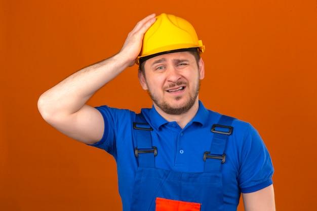 Budowniczy mężczyzna w mundurze konstrukcyjnym i hełmie ochronnym z ręką na głowie za pomyłkę pamięta błąd zapomniał złej koncepcji pamięci na izolowanej pomarańczowej ścianie
