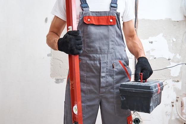 Budowniczy mężczyzna w mundurze z narzędziami budowlanymi. koncepcja naprawy