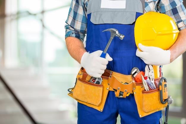 Budowniczy mężczyzna w średnim wieku z młotkiem na rozmytym tle