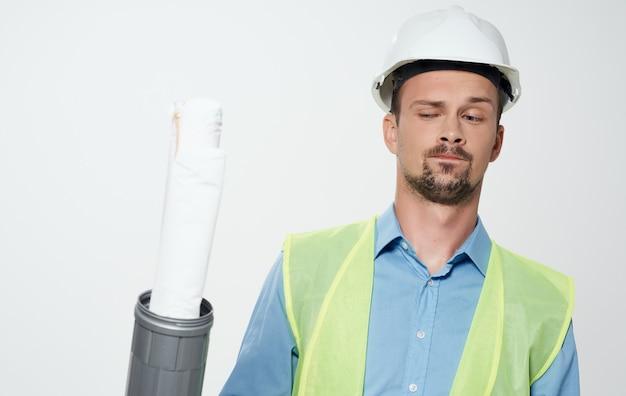 Budowniczy mężczyzna w żółtej kamizelce i białym hełmie z rolką papieru w ręku, prace naprawcze.
