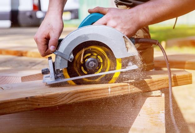 Budowniczy piłuje deskę za pomocą piły tarczowej tnącej drewnianą deskę