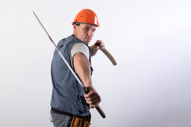 Budowniczy pokazuje walkę kataną. mechanik w kasku i odzieży roboczej. w dowolnym celu.