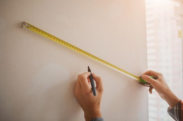 Budowniczy pracuje na budowie i mierzy ścianę. pracownik w pomarańczowym kasku budowlanym dokonuje napraw w domu
