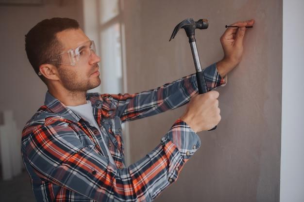 Budowniczy pracuje na budowie. pracownik z wiadrem i wałkiem do malowania w pobliżu ściany.