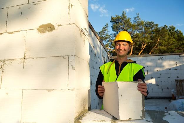 Budowniczy trzyma w rękach blok betonu komórkowego - mury ścian domu. robotnicy budowlani w odzieży ochronnej - kask i kamizelka odblaskowa.
