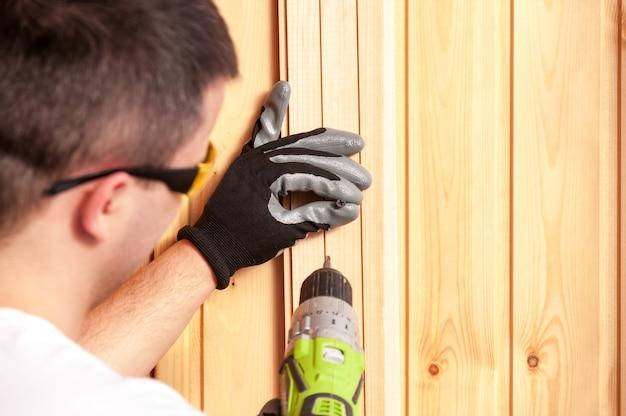 Budowniczy trzyma w ręku elektryczny śrubokręt na tle betonowej ściany.