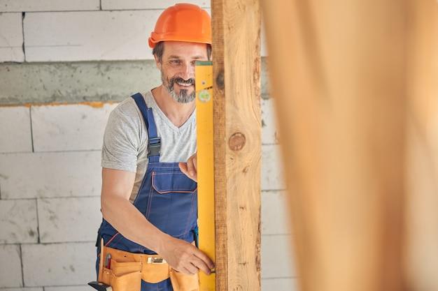 Budowniczy umieszczający poziomicę na powierzchni obiektu