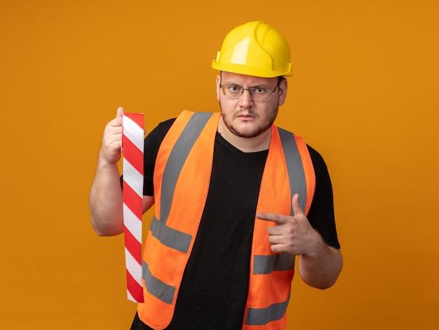 Budowniczy w kamizelce budowlanej i kasku ochronnym, trzymający taśmę klejącą wskazującą palcem wskazującym