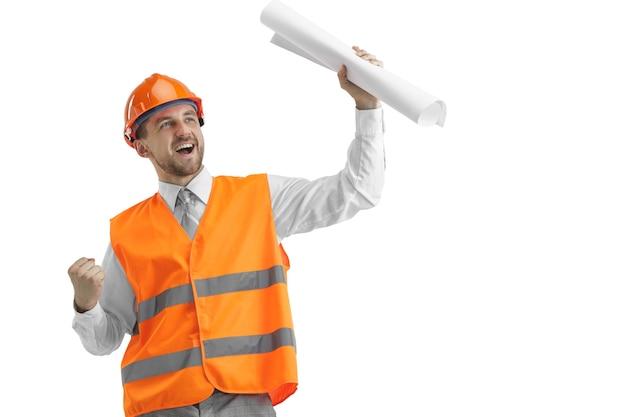 Budowniczy w kamizelce budowlanej i pomarańczowym hełmie stojącym na białej ścianie. specjalista ds. bezpieczeństwa, inżynier, przemysł, architektura, kierownik, zawód, biznesmen, koncepcja pracy