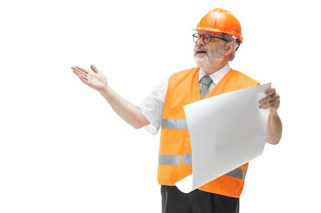 Budowniczy w kamizelce budowlanej i pomarańczowym hełmie stojącym na białym tle.