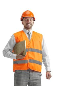 Budowniczy w kamizelce budowlanej i pomarańczowym hełmie z laptopem.