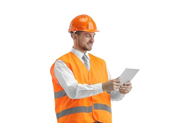 Budowniczy w kamizelce budowlanej i pomarańczowym hełmie z tabletem. specjalista ds. bezpieczeństwa, inżynier, przemysł, architektura, kierownik, zawód, biznesmen, koncepcja pracy