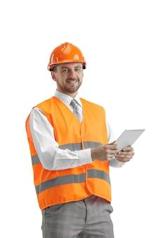 Budowniczy w kamizelce budowlanej i pomarańczowym hełmie z tabletem.