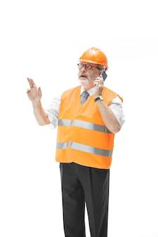 Budowniczy w kamizelce budowlanej i pomarańczowym kasku rozmawia o czymś przez telefon komórkowy