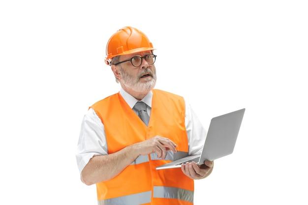 Budowniczy w kamizelce budowlanej i pomarańczowym kasku z laptopem. specjalista ds. bezpieczeństwa, inżynier, przemysł, architektura, menedżer, zawód, biznesmen, koncepcja pracy