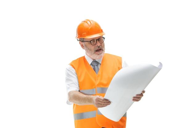 Budowniczy w kamizelkę budowlaną i pomarańczowy kask stojący na białym tle.