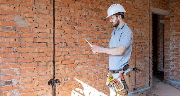 Budowniczy w odzieży roboczej bada rysunek konstrukcyjny na placu budowy.