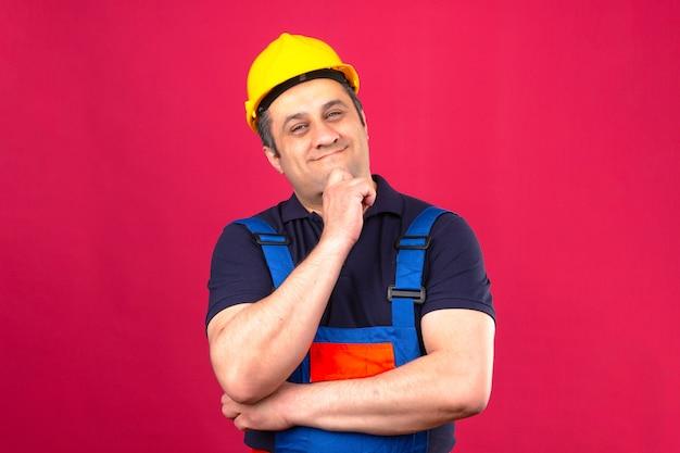 Budowniczy w średnim wieku zamyślony mężczyzna ubrany w mundur konstrukcyjny i hełm ochronny, patrząc pewnie i uśmiechnięty dotykając brodę stojącą nad izolowaną różową ścianą