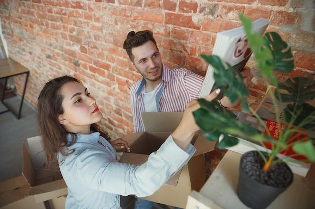 Buduj przyszłość. młoda para przeprowadziła się do nowego domu lub mieszkania. wyglądaj na szczęśliwego i pewnego siebie. rodzina, przeprowadzka, relacje, pierwsza koncepcja domu. rozpakuj ich pudełka z książkami i roślinami, połóż je na półkach.
