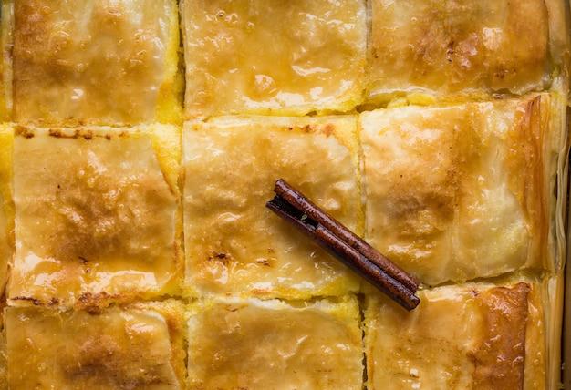 """Budyń grecki tradycyjny deser """"galaktoboureko"""" lub bougatsa zapiekany na patelni z syropem. widok z góry, zbliżenie"""