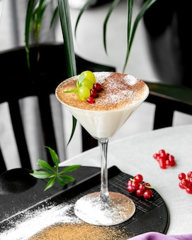 Budyń waniliowy podawany w kieliszku martini udekorowanym czerwoną porzeczką i winogronami