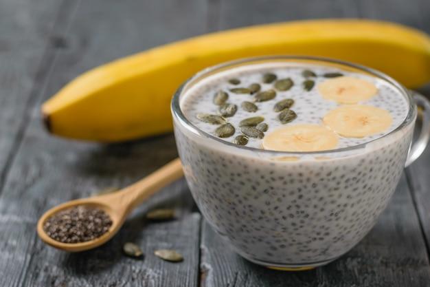 Budyń z nasion chia z bananem i pestkami dyni na ciemnym drewnianym stole.
