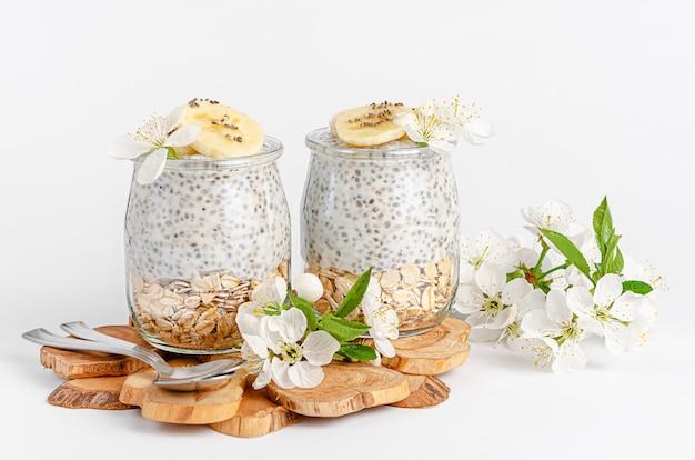 Budyń z nasion chia z jogurtem i owsem na białej ścianie ozdobiony kwiatami. koncepcja superfood. skopiuj miejsce