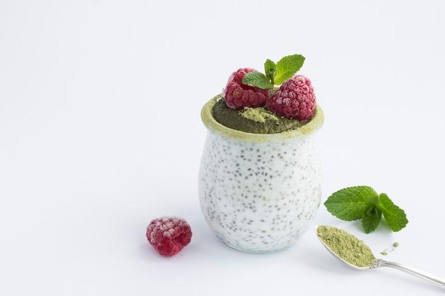 Budyń z nasion chia z malinami i herbatą matcha w szklanym słoju na białym tle. zbliżenie. skopiuj miejsce.