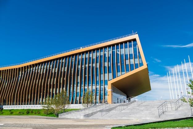 Budynek biurowy na łące ze szklanymi oknami, które odbijają pływające chmury, wzdłuż budynku są ludzie