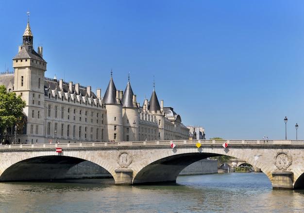 Budynek conciergerie w paryżu widok z brzegu rzeki sekwany z mostu invalides