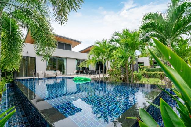 Budynek domu lub domu na zewnątrz i wnętrza przedstawiający tropikalną willę z basenem z zielonym ogrodem