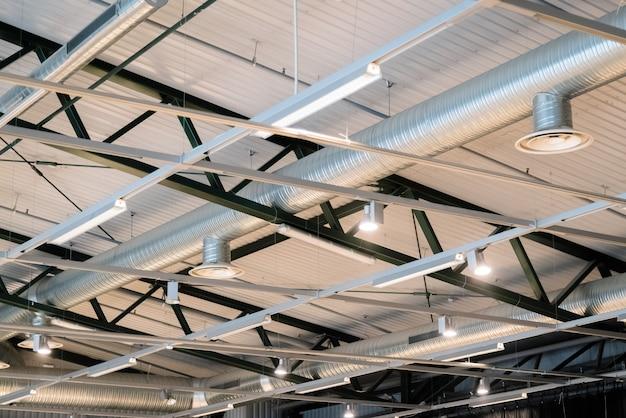 Budynek fabryczny lub budynek magazynowy. ogromna pusta przestrzeń z rurami wentylacyjnymi i światłami