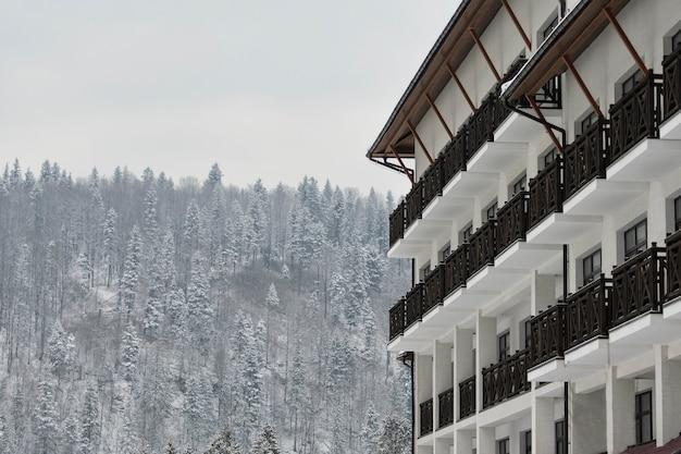 Budynek hotelu na tle pokrytych śniegiem drzew iglastych. miejsce na tekst.