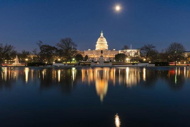Budynek kapitolu stanów zjednoczonych w czasie zmierzchu z super pełni księżyca odbiciem z dużym basenem, waszyngton, dc, usa
