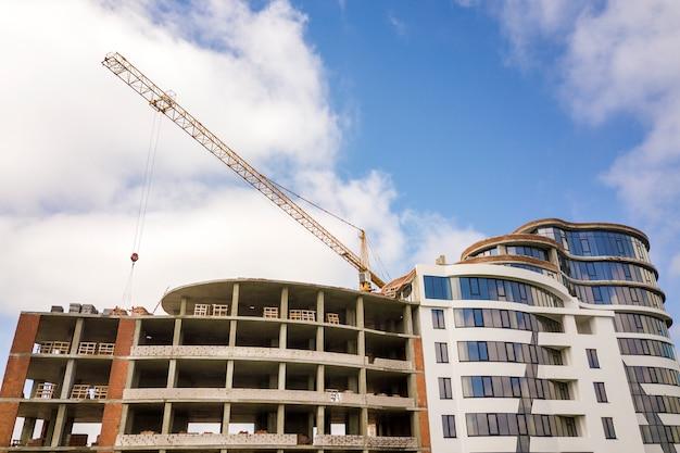 Budynek mieszkalny lub biurowy w budowie. ceglane ściany, szklane okna, rusztowania i betonowe filary wsporcze. basztowy żuraw na jaskrawym niebieskie niebo kopii przestrzeni tle.