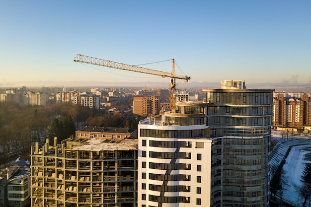 Budynek mieszkalny lub biurowy wysoki budynek w budowie, widok z góry. basztowy żuraw na jaskrawej niebieskie niebo kopii przestrzeni, miasto krajobrazowy rozciąganie horyzont. fotografia lotnicza dronów.